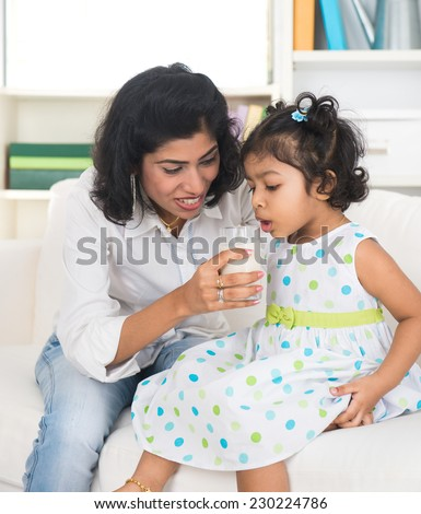 indian mother and child drinking milk - stock photo