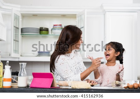 Indian mother and daughter having fun when cooking - stock photo