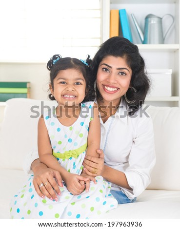 indian mother and daughter smiling indoor in the living room - stock photo
