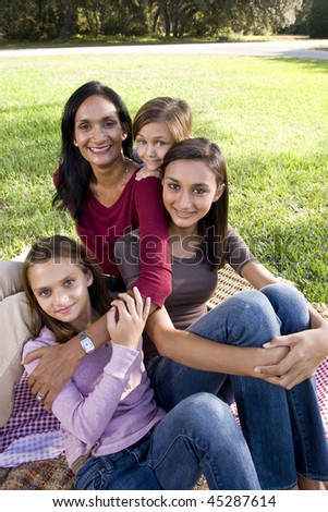 Indian mother and three children enjoying family picnic in park on sunny day - stock photo