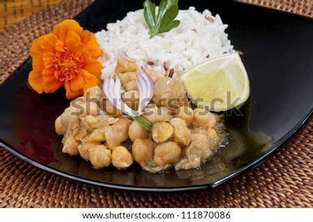Indian or Thai chickpea curry on a black plate with fresh basmati rice garnished with a marigold flower, lime and red onion-  On a woven mat - stock photo