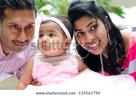 Indian parents and baby girl at outdoor home garden - stock photo