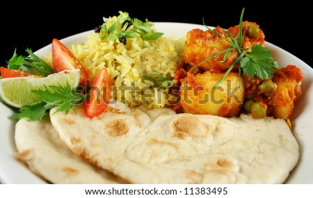Indian pea and potato curry with tumeric rice and a side salad. - stock photo