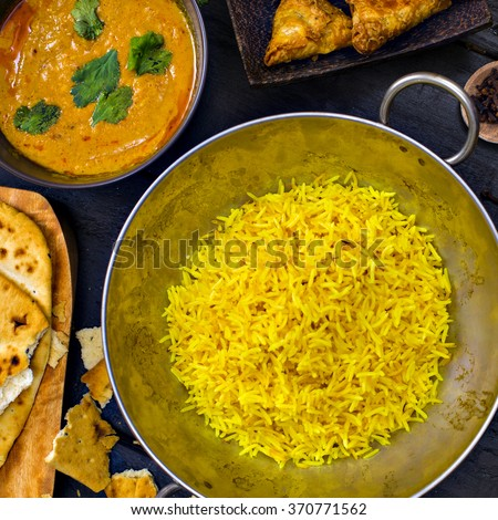 Indian pilau rice in balti dish served with chicken tikka masala curry, plain naan bread, vegetable samosas, and onion bhajis - stock photo
