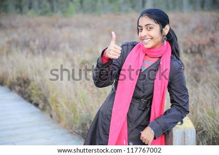Indian pretty girl showing thumbs up in autumn park