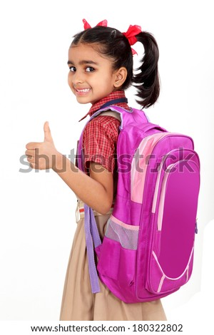 Indian primary school girl in uniform with school bag over shoulder. Isolated on white. - stock photo