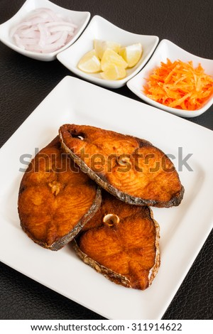 Indian seer fish fillets fry - Closeup of delicious seer/mackerel fish fillets fry served with shredded carrots, raw onion rings, lemon. The fish is marinated in cayenne pepper, salt and deep fried. - stock photo
