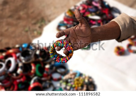 Indian seller showing various of Indian bracelets at market in Kochi, Kerala, India - stock photo