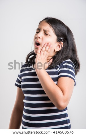indian small girl and toothache, sad indian little girl with tooth pain, stressful indian girl with  paining tooth, indian girl suffering from toothache, indian girl with dental problem - stock photo