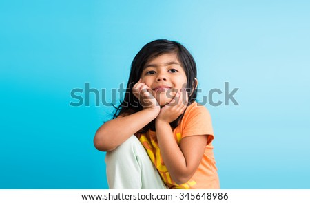 Indian small girl portrait, both hands on chin, casual expression, cute smile, mild smile, blue background, indian little girl, 4 years age,black and long hair - stock photo