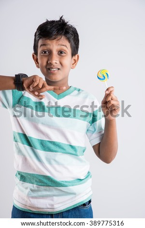 indian small girl with lolipop or loly pop, asian girl and lolipop or lolypop, playful indian cute girl posing with lolipop or candy - stock photo