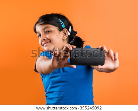 indian small girl with mobile, asian small girl with mobile, indian girl child and mobile, asian girl clild and mobile, indian small girl posing with mobile, indian girl playing with mobile, selfie - stock photo