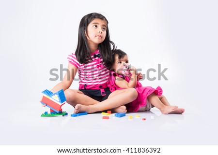 indian small girls or asian small siblings playing with colourful blocks over white background, cute little indian girl baby sitting or taking care of younger sister, two small indian sisters playing - stock photo