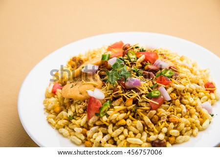 Indian snacks Bhel Puri served with chopped tomatoes, green chillies, coriander leaves