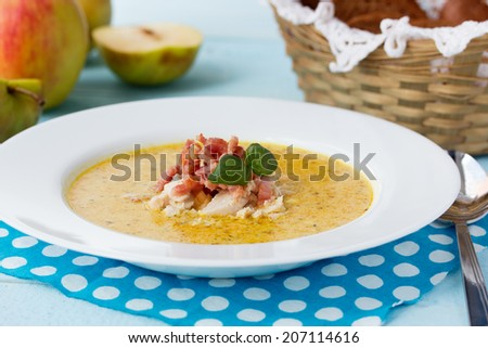 Indian soup Potage Mulligatawny with apple curry, bacon and basil in white soup bowl on blue desk with polka dot napkin