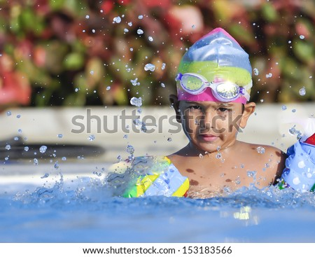 Indian South Asian origin boy having a good time in Arab resort swimming pool - stock photo