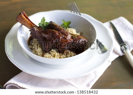 Indian spiced, braised lamb shank over cous cous. - stock photo