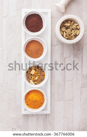 Indian spices with mortars and pestle. Indian spices: curry, turmeric, sumac, cardamom and tandoori. over rustic background.  Top view, blank space, vintage toned image. Natural light - stock photo