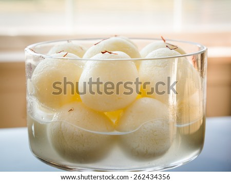 Indian sweet. Rasgulla is a syrupy dessert popular in the Indian subcontinent, and is made out of Indian cottage cheese and sugar syrup.Creative abstract lighting and selective focus - stock photo