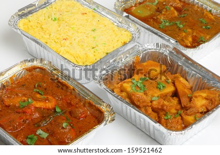 Indian takeaway food selection in foil containers. - stock photo