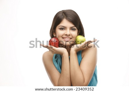 indian teenage girl holding the red and green apples near her cheeks - stock photo