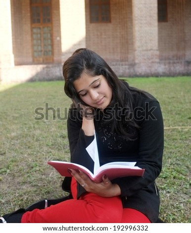 Indian teenager reading a book. - stock photo