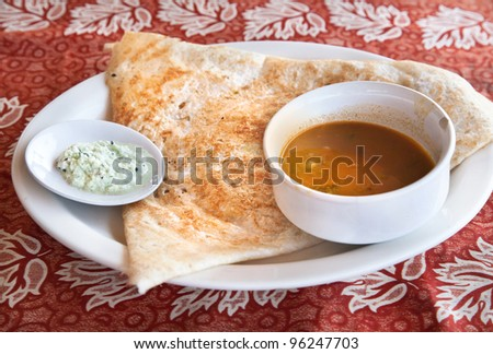 Indian traditional vegetarian masala dosa with potato inside, sambar and coconut chutney nearby at Indian restaurant - stock photo