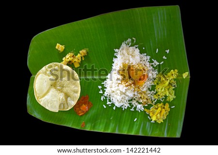 Indian traditional vegetarian thali from rice, dal, potatoes, tomato salad and two puri on banana leaf isolated on black background - stock photo
