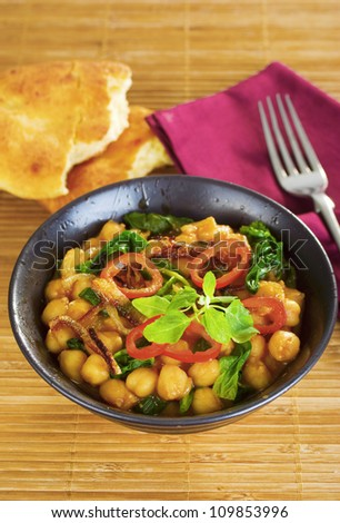 Indian vegetarian curry, with chickpeas, or garbanzo beans, with spinach, capsicums and crisply fried onions. - stock photo