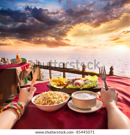 Indian vegetarian sizzler, corn soup and fried rice on the table at ocean and dramatic sunset background. Hands with fork and knife on the table - stock photo