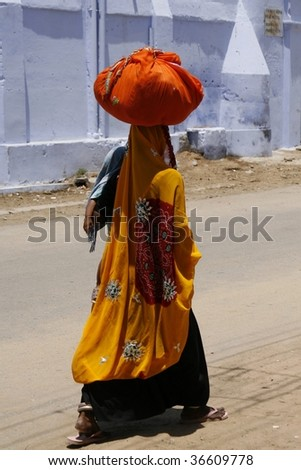 Indian woman carrying a bundle on her head and a child on her hands. Pushkar region, India.