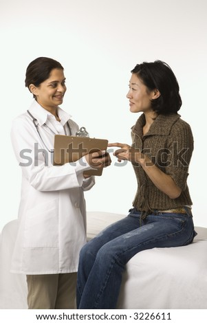 Indian woman doctor with Asian woman patient. - stock photo
