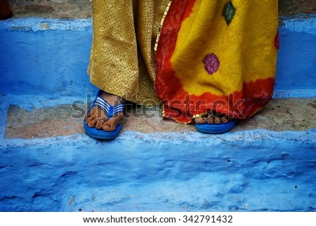 Indian woman in a sari standing on blue steps.
