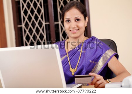 Indian woman shopping online with credit card and laptop.