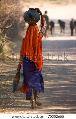 Indian woman walking home from the well with water carried in a pot on her head near Udaipur in India January 2007/Carrying water home in India - stock photo