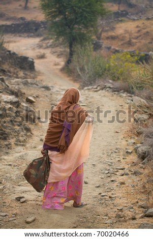 Indian woman walking to market in rural India - stock photo