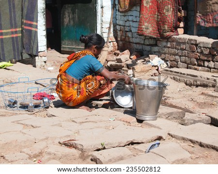 Indian woman washing dishes on the street         - stock photo