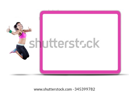 Indian woman wearing sportswear jumping near the empty board while showing thumbs up - stock photo