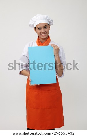 Indian woman with chef uniform holding a blank card - stock photo