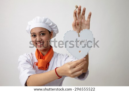 Indian woman with chef uniform holding a welcome signage - stock photo