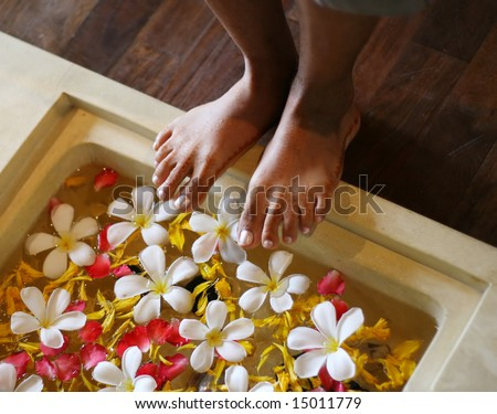 Indian woman (with henna) about to soak her feet in water decorated with flowers.