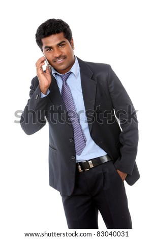 Indian young business man talking in mobile phone at office - stock photo