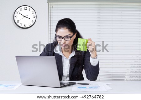 Indian young businesswoman looks busy, working in the office while enjoying a cup of coffee and using a laptop