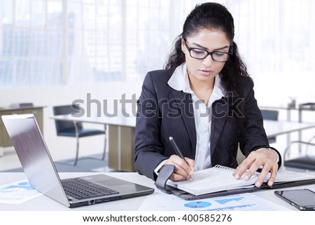 Indian young businesswoman working in the office with laptop computer and writes a journal on the notebook - stock photo
