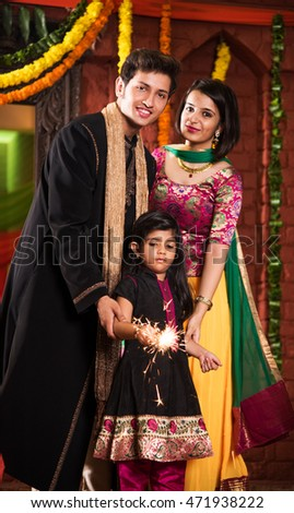 Indian young couple and daughter celebrating diwali festival with firecrackers