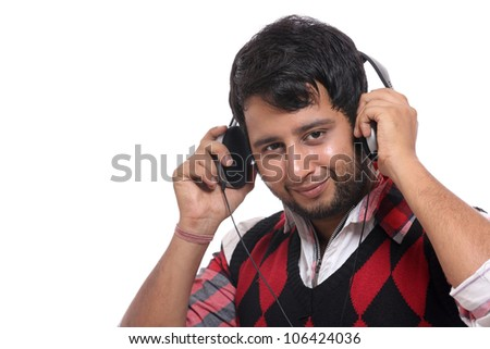 Indian young man with headphone on white background.