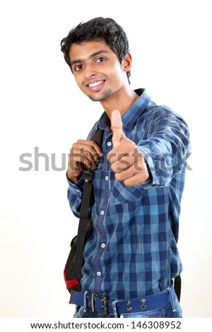 Indian young student carrying bag on white and  showing  thumbs up. - stock photo
