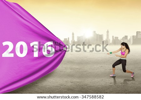 Indian young woman pulling a big banner with numbers 2016 while wearing sportswear, shot outdoors - stock photo