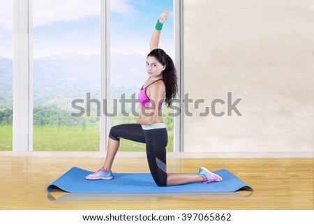 Indian young woman using a mat on the floor and doing stretching exercise at home