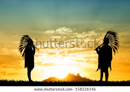 Indians playing music at sunset - stock photo